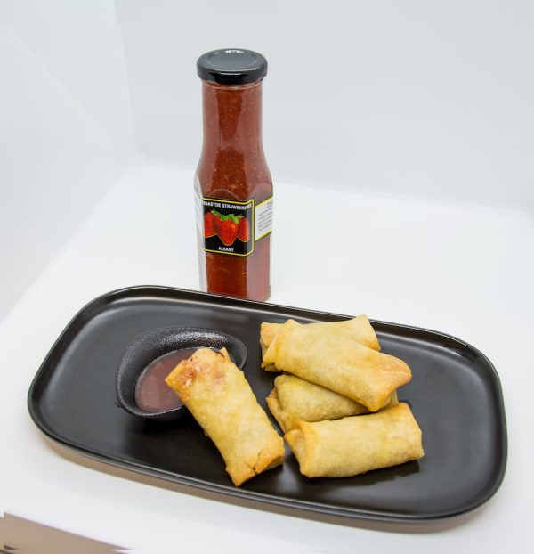 A bottle of strawberry chilli sauce and a small plate of spring rolls
