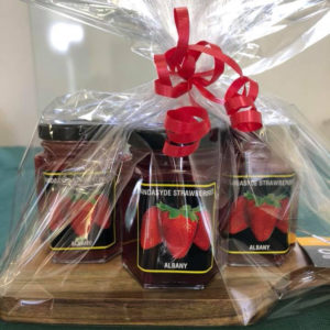 A gift pack of three jars of jam on a wooden chopping board wrapped in clear celophane